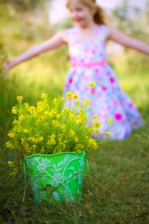 Happy little girl and a bucket of flowers in  park photo