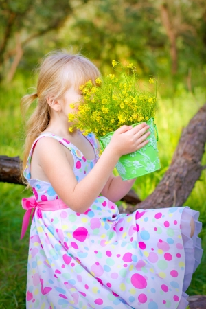 olfaction: Little girl sitting on a branch of  tree and smelling the flowers