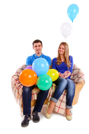 Friends sitting on a sofa with balloons isolated photo