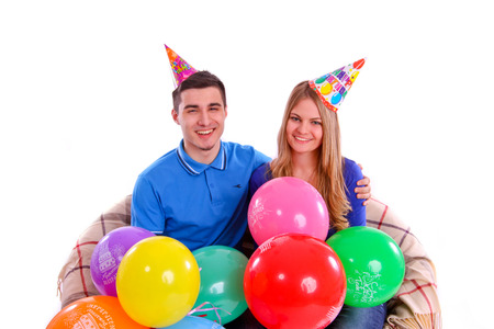 Friends sitting on a sofa with balloons and hats photo