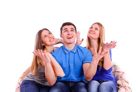 Guy and two girls sitting on the couch and looking up isolated photo