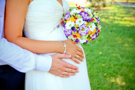 hands with rings and bouquet outdoors photo