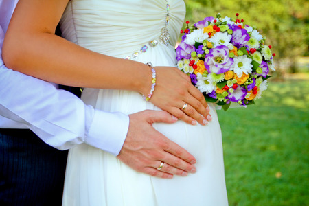 hands with rings and bouquet outdoors