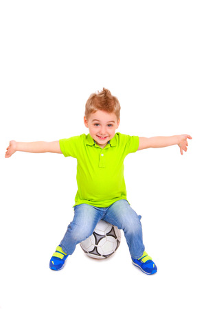 Happy little boy sitting on a soccer ball isolated photo
