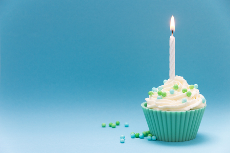 cupcake with burning candle and blue background Stock fotó