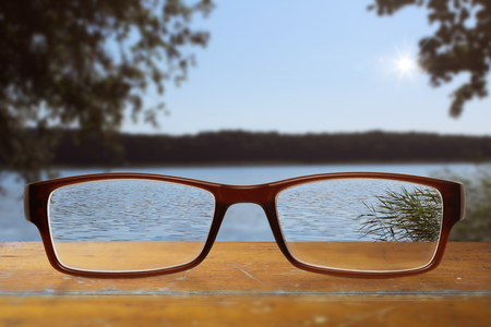 black modern glasses on wooden table with blue sky and lake in the background