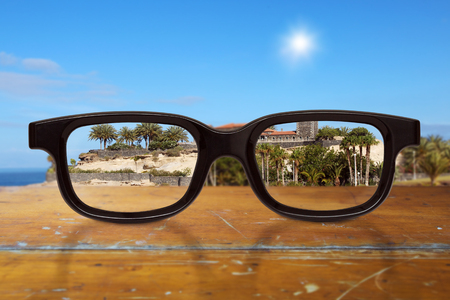 black modern black glasses on wooden table with blue sky and building