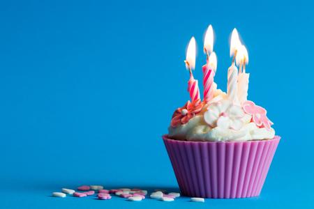 Pink birthday cupcake on blue background