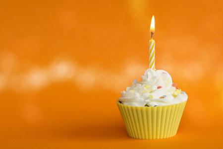 yellow cupcake on orange background Stock Photo