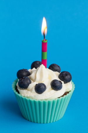 Green birthday cupcake with blueberries on blue background
