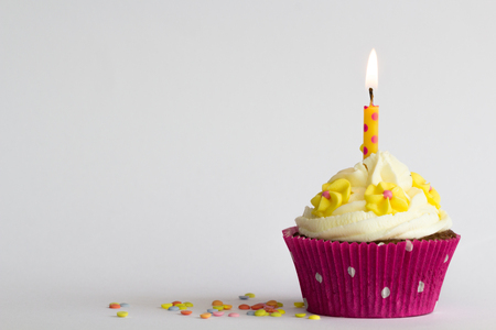 Delicious birthday cupcake with flowers and candle
