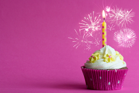 pink happy new year cupcake with burning candle stock photo 77440595