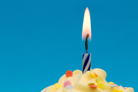 Burning candle on cupcake close-up