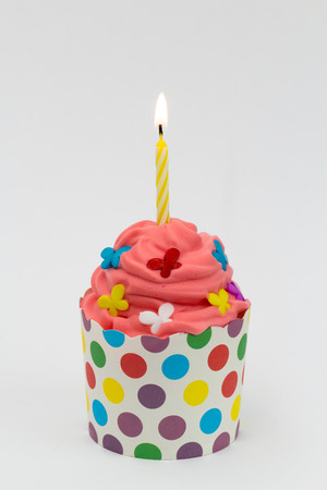 Colorful party cupcake with burning candle Stock Photo