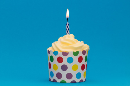 Cupcake with burning candle against blue background Stock Photo