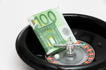 roulette wheel with 100 euro banknote on white background Stock Photo