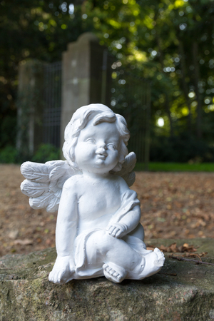 angel statue sitting on a stone