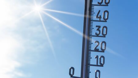 Bright sun with thermometer. Summer background Stock Photo