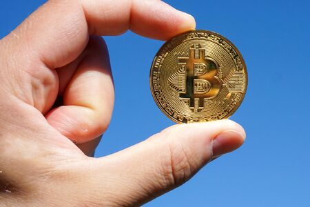 Hand holding bitcoin coin