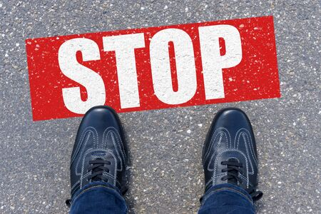 Top view of business shoes on the floor with the text: STOP