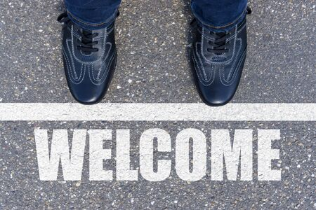 Welcome message on asphalt and business shoes Stock Photo