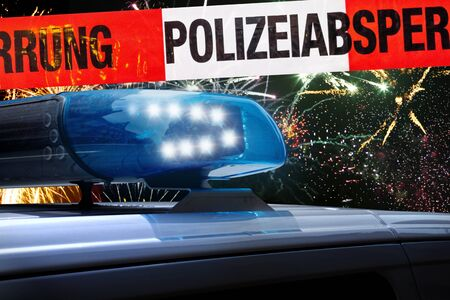 German police car in front of fireworks stands behind cordon tape with the word? Polizeiabsperrung ?, the German word for police cordon