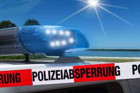 German police car on the beach behind cordon tape with the word? Polizeiabsperrung ?, the German word for police cordon