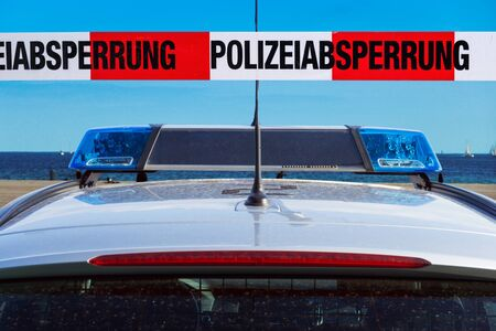 German police car on the beach cordon tape with the word? Polizeiabsperrung ?, the German word for police cordon