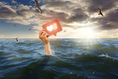 Single hand of drowning man in sea holding his Like icon