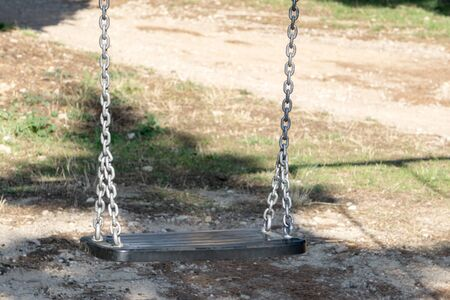 Empty swing in a park on a sunny day Stock Photo