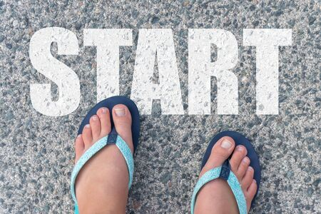 Top view of bare feet in flip-flops on the floor with the text: START