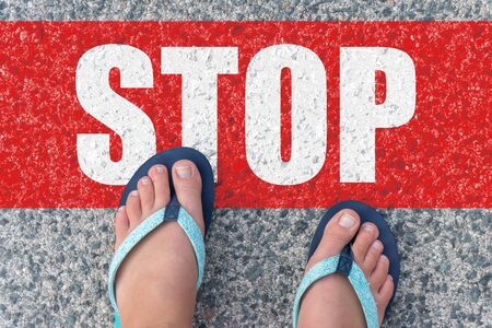Top view of bare feet in flip-flops on the floor with the text: STOP