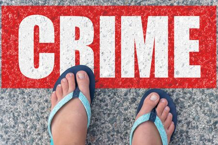 Top view of naked female feet in flip-flops on the floor with the text: CRIME Stock Photo