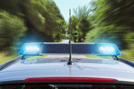 Police car driving on country road Stock Photo