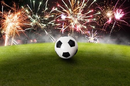 Soccer ball on grass with beautiful fireworks