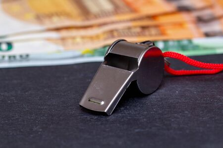 Metal whistle on slate in front of euro banknotes Archivio Fotografico