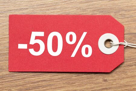 Red paper tag labeled with -50% word isolated on wooden background