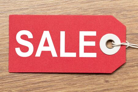 Red paper tag labeled with SALE word isolated on wooden background