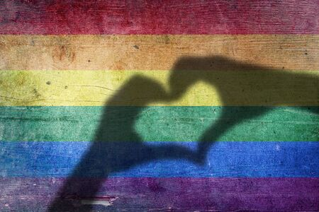 Shadows of hands forming a heart on colorful rainbow painted wood planks background Stock Photo