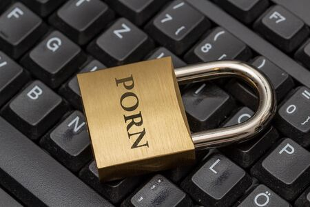 Padlock with the word PORN on black computer keyboard