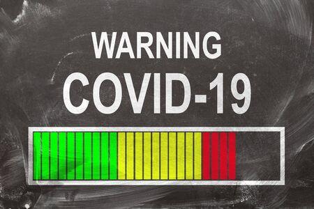 Warning Covid-19 written on chalkboard