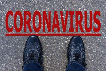 Word CORONAVIRUS written on asphalt with shoes, concept background