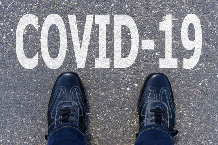 Word COVID-19 written on asphalt with shoes, concept background
