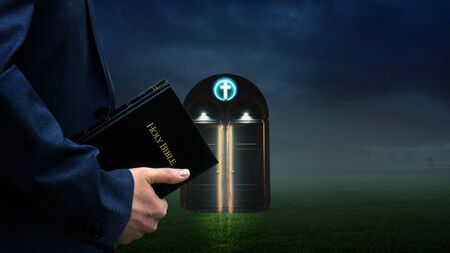 Man holding Bible in front of a glowing church door