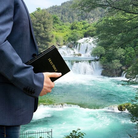 Man in a park with a bible