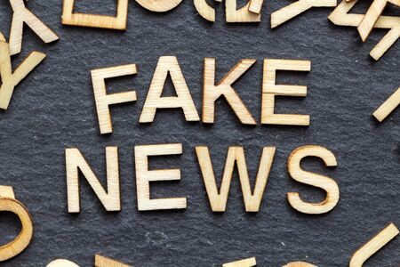 Wooden letters FAKE NEWS on slate background Stock Photo