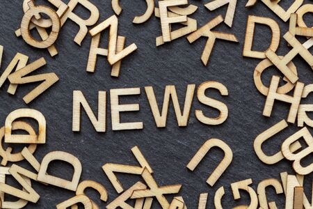 Wooden letters NEWS on slate background