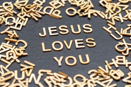 Wooden letters JESUS LOVES YOU on slate background Stock Photo