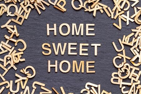 Wooden letters HOME SWEET HOME on slate background