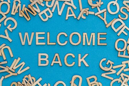 Wooden letters WELCOME BACK on blue background